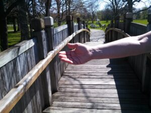 Hand outstretched across a wooden bridge