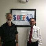Two people in front of SDFF sign